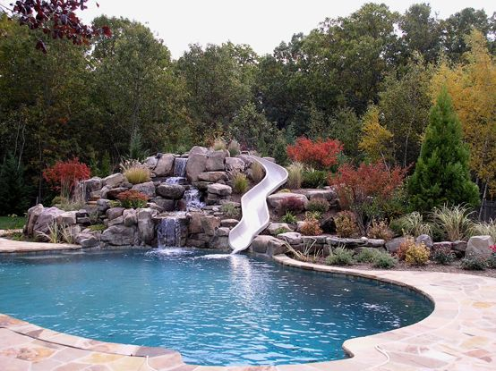 Pool slide love the privacy the stone wall and for Swimming pool designs with slides