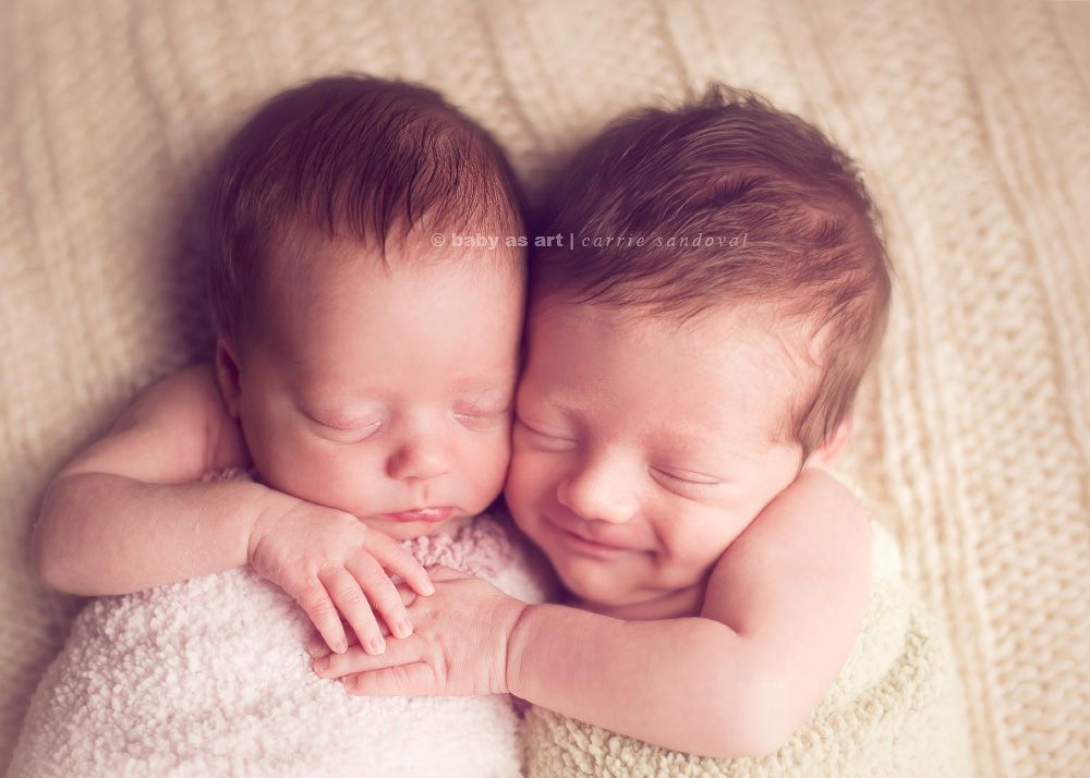 Newborn twins hugging look at the smile