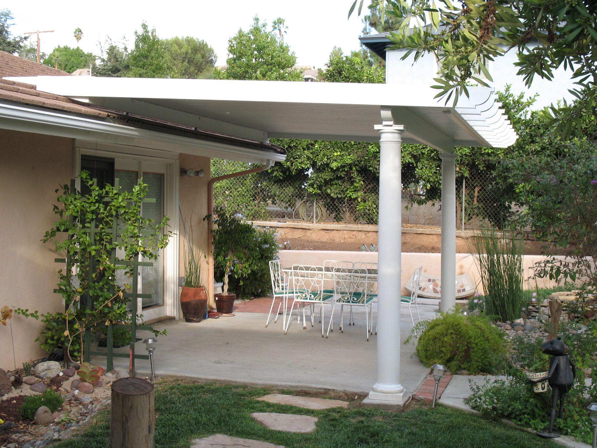 Marvelous White Round Column With White Wooden Sloping Roofing And White Patio Set Decors As