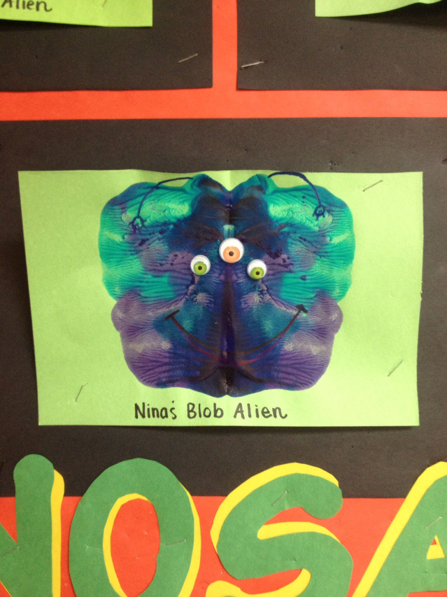 Blob Aliens made by folding paper in half, opening it back up and letting children drip different colored paint on one side. Children then fold the paper back in half and smooth the paper to spread the paint. Open it up and draw on and alien face or glue googly eyes!