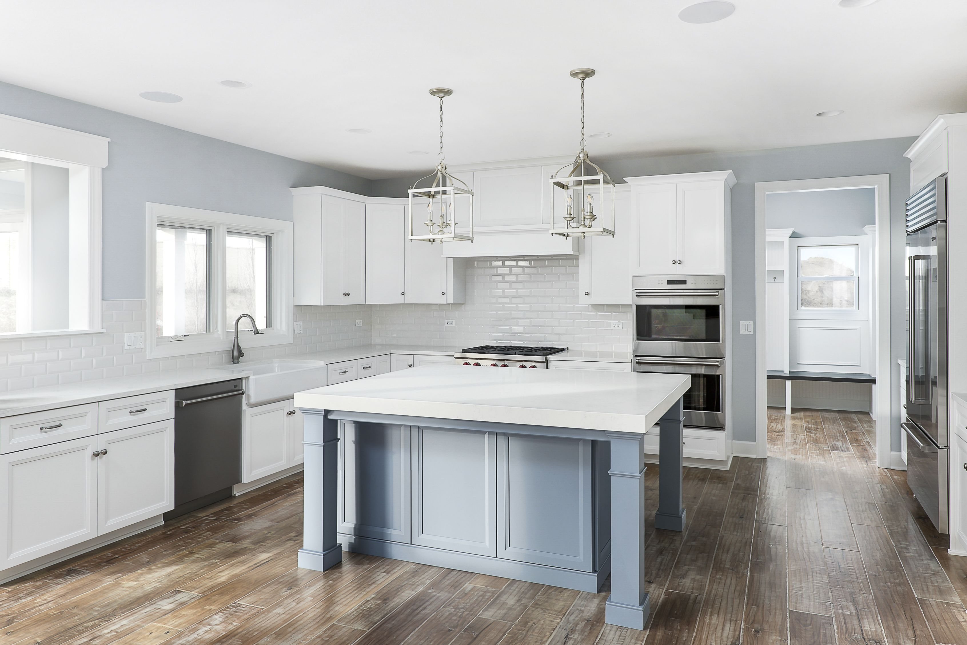 White Cabinets And Blue Gray Island Combine For A Casual Elegance In This Custom Built Home By King S Court Bu Custom Homes Kitchen Remodel Custom Home Designs