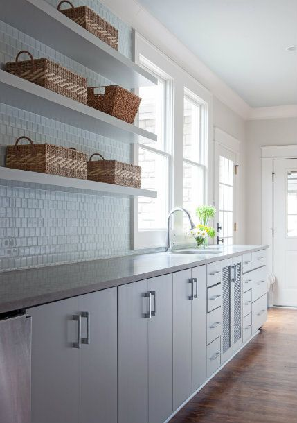 Long kitchen features white flat front cabinets paired ...