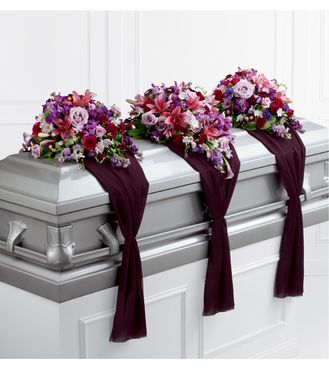 The center arrangement consists of lavender roses, dark pink Asiatic lilies, pink mini calla lilies, lavender freesia, purple and lavender stock, fuchsia carnations and mini carnations, purple mokara orchids, and purple matsumoto asters. The two end pieces