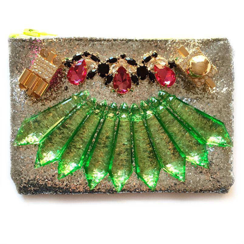 -BOLSO KRIPTON- Bolso pequeño, tipo clutch, de tela glitter en color plata y cremallera verde flúor. En la parte delantera lleva piedras en talla pera de color negro y fucsia, incrustaciones de resina verde y dos accesorios metálicos dorados. Medidas: 25,5 cm largo x 18 cm ancho. Precio: 70€ #handbag #clutch #fadvondaiz #bolsokripton