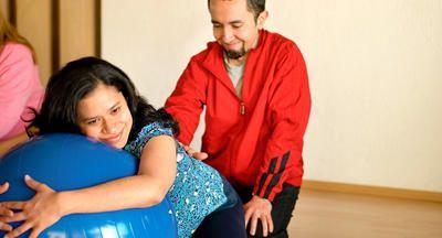 mujer embarazada apoyándose sobre pelota de ejercicios mientras marido la mira