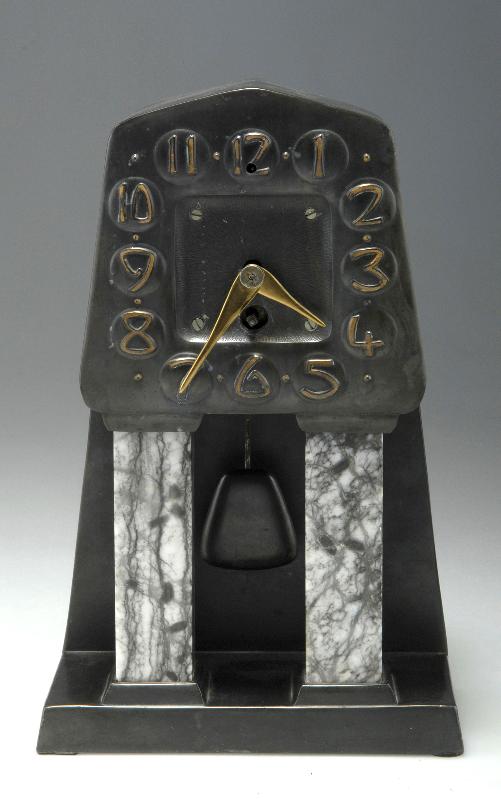 Albin Müller. Table clock, 1906. H. 31 cm; 19.2 x 11.2 cm. Made by Fürstlich Stolbergsches Hüttenamt, Ilsenburg. Cast iron, black patina, brass, white-grey Alabaster.