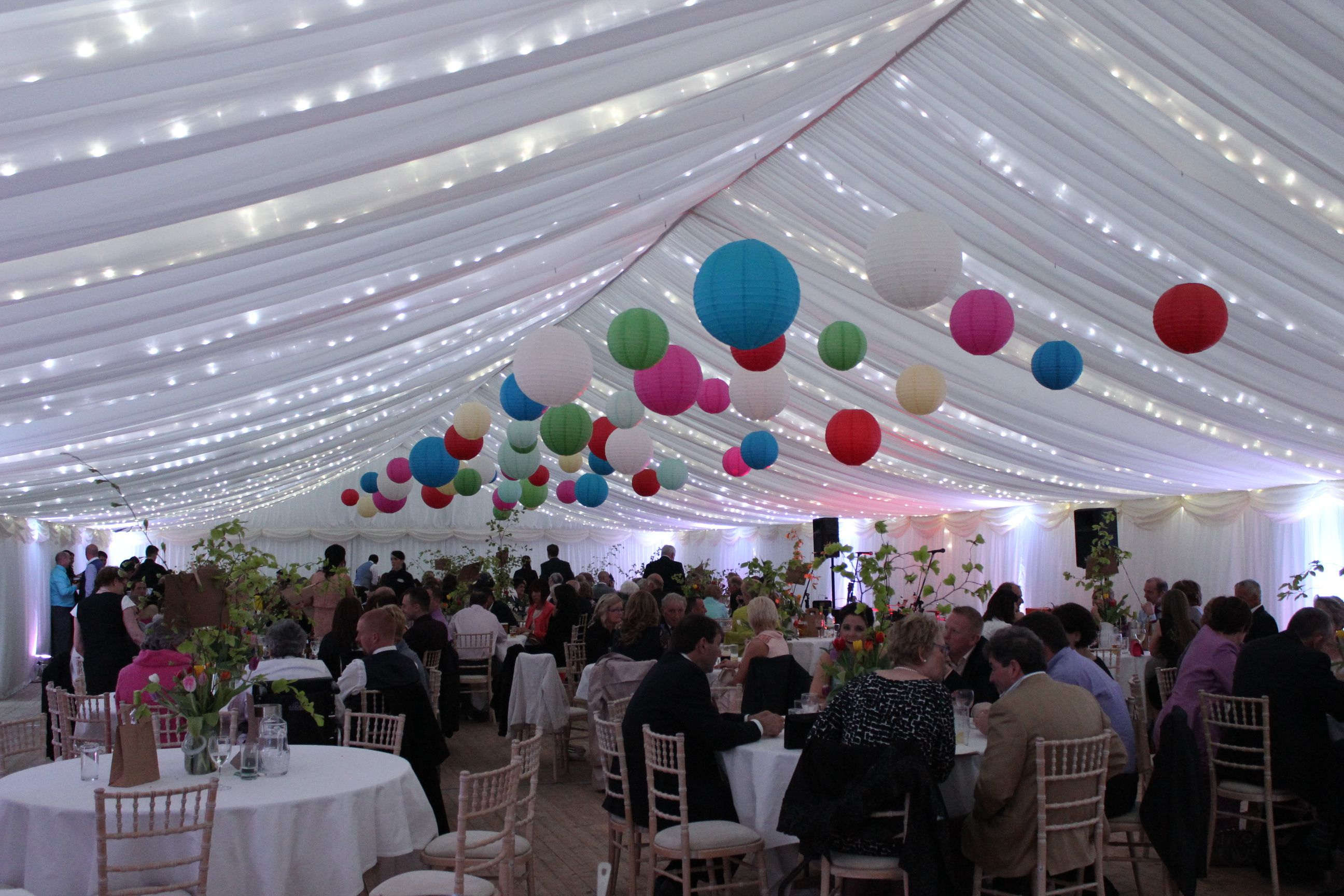 Colourful paper lanterns and fairy lights in the ceiling of the Marquee. Designed to 'Welcome Spring'