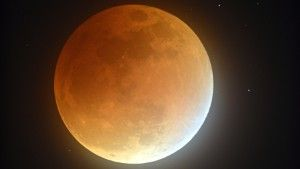 In this photo taken with a long exposure, Earth's shadow partially obscures the view of the so-called supermoon during a lunar eclipse in Stedman, N.C., Sunday, Sept. 27, 2015. It was the first time Sunday that the events have made a twin appearance since 1982, and they won't again until 2033. (Johnny Horne/The Fayetteville Observer via AP) MANDATORY CREDIT