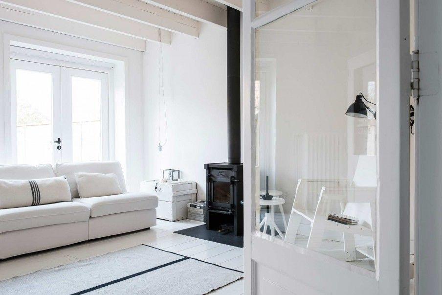 Witte woonkamer met zwarte open haard | White living area with black ...