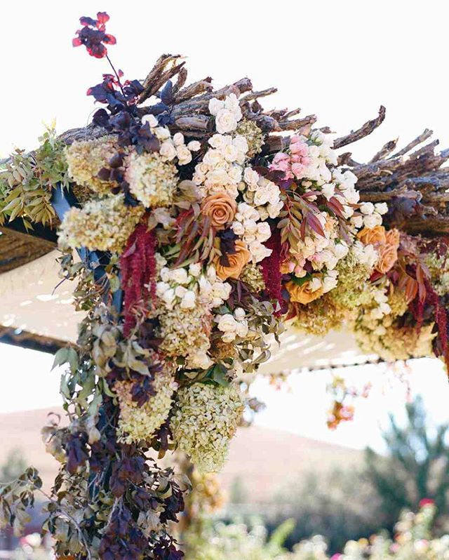chuppah dripping in flowers in the fall harvest color scheme