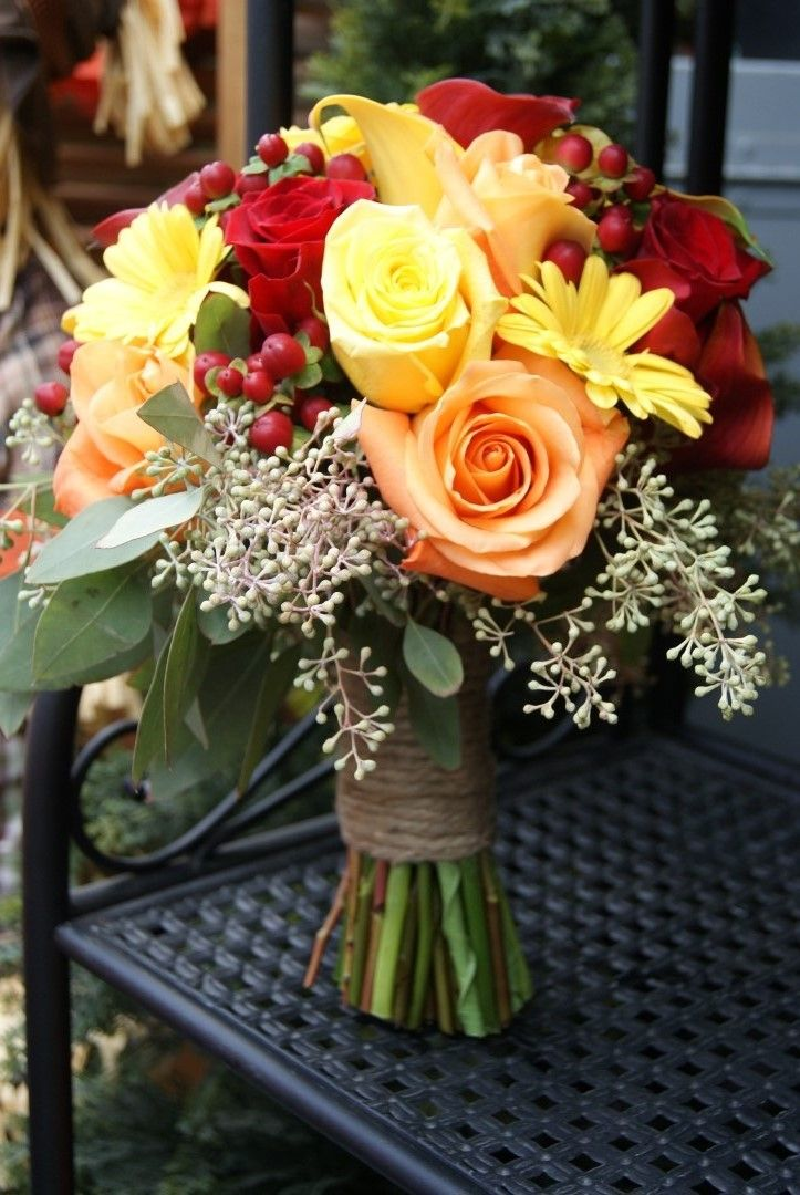 Gorgeous fall wedding bouquet!  Made of peach, yellow, and red roses, hypericum berries, mini gerberas, yellow and red callas, and seeded eucalyptus greenery