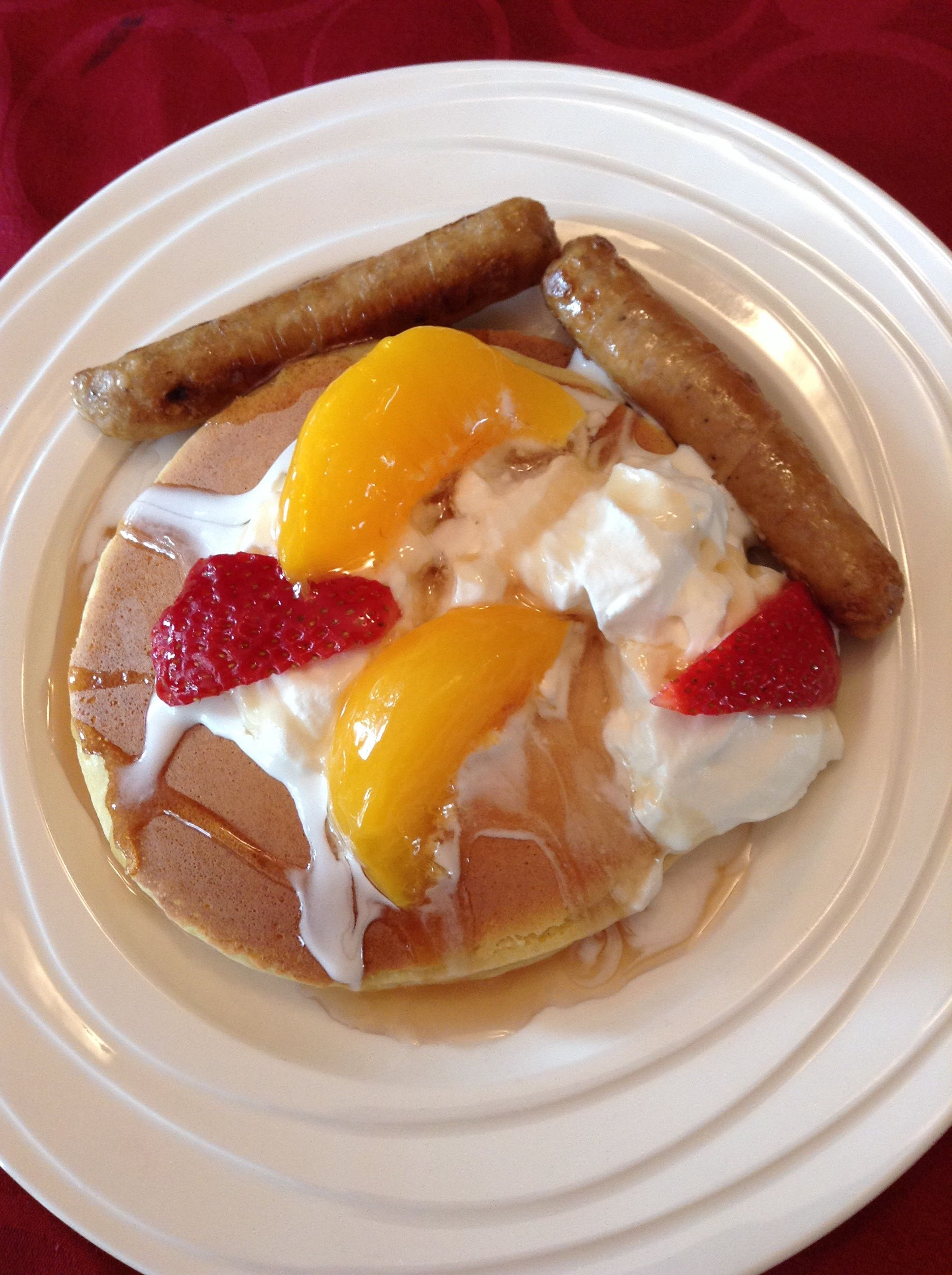 Yummy pancake,sausage,peach,straw berry,syrup and to top it all off with whip cream so good of a breakfast!