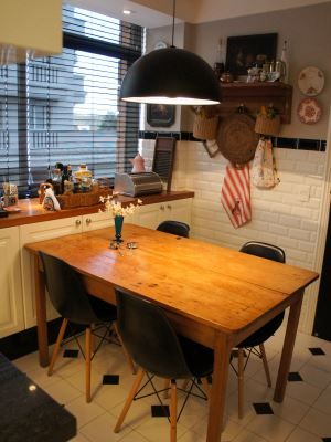 Cozinha com pendente preto e mesa de madeira: composição criou um efeito harmônico.
