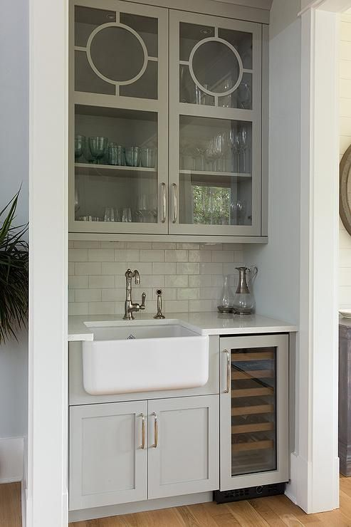 Wet Bar With A Farmhouse Sink May Be Small But Does Not Lack Style Gray Glass Front Wet Bar Cabinets Showcas Wet Bar Cabinets Kitchen Wet Bar Wet Bar Basement