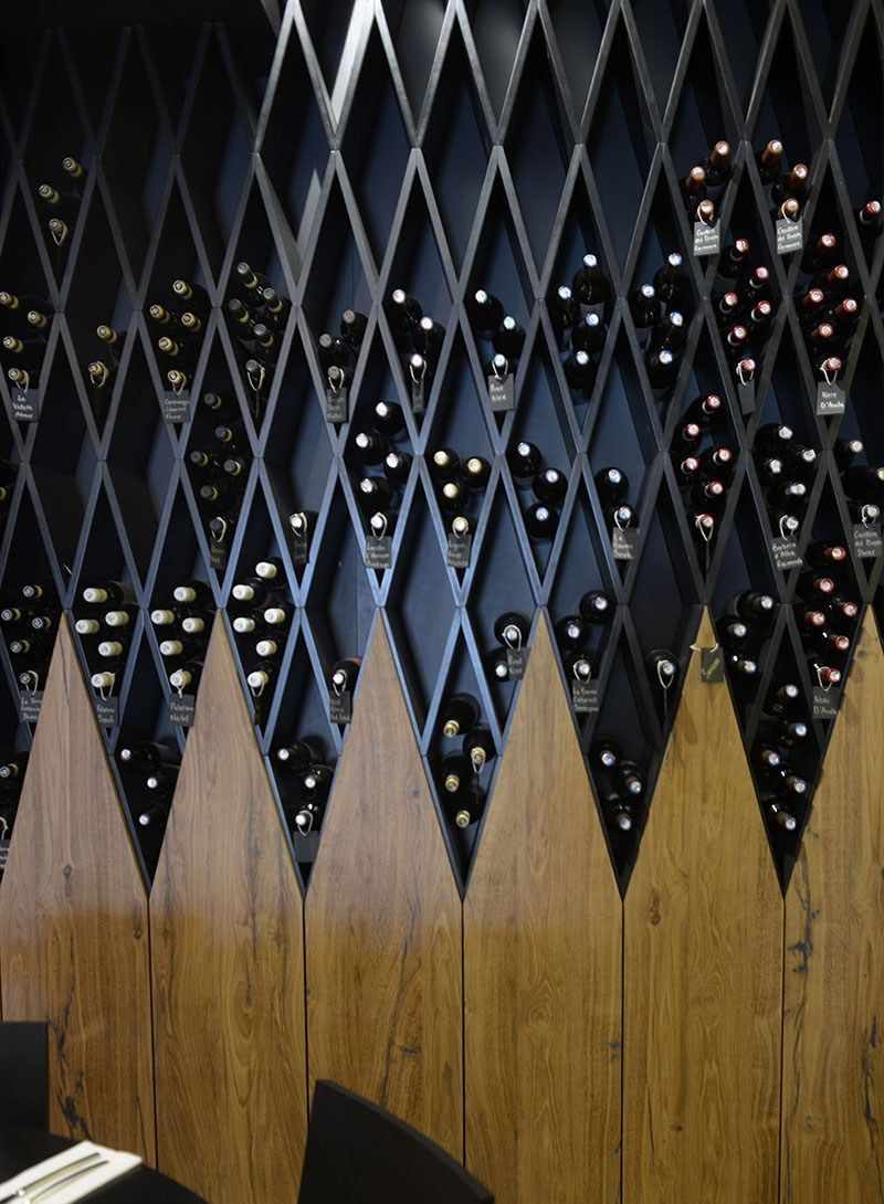 A Wine Wall Made Of Diamond Shaped Shelves