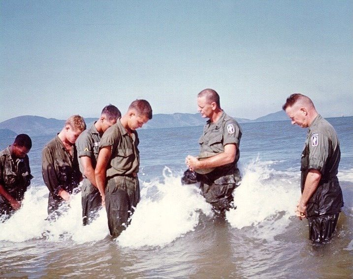 Soldiers getting baptised in the sea by U.S. Army Chaplain John Watters. Father Watters served in the New Jersey National Guard before joining the active duty Army. He was the nephew of Navy Boatswain's Mate John J. Doran who received the Medal of Honor in the Spanish-American War. WW2.