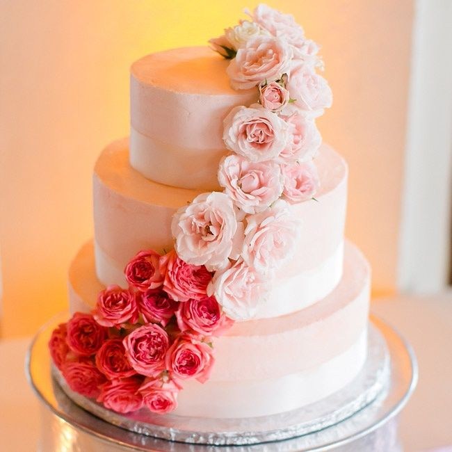 A three-tiered round cake was topped with cascading roses in blush and hot pink.