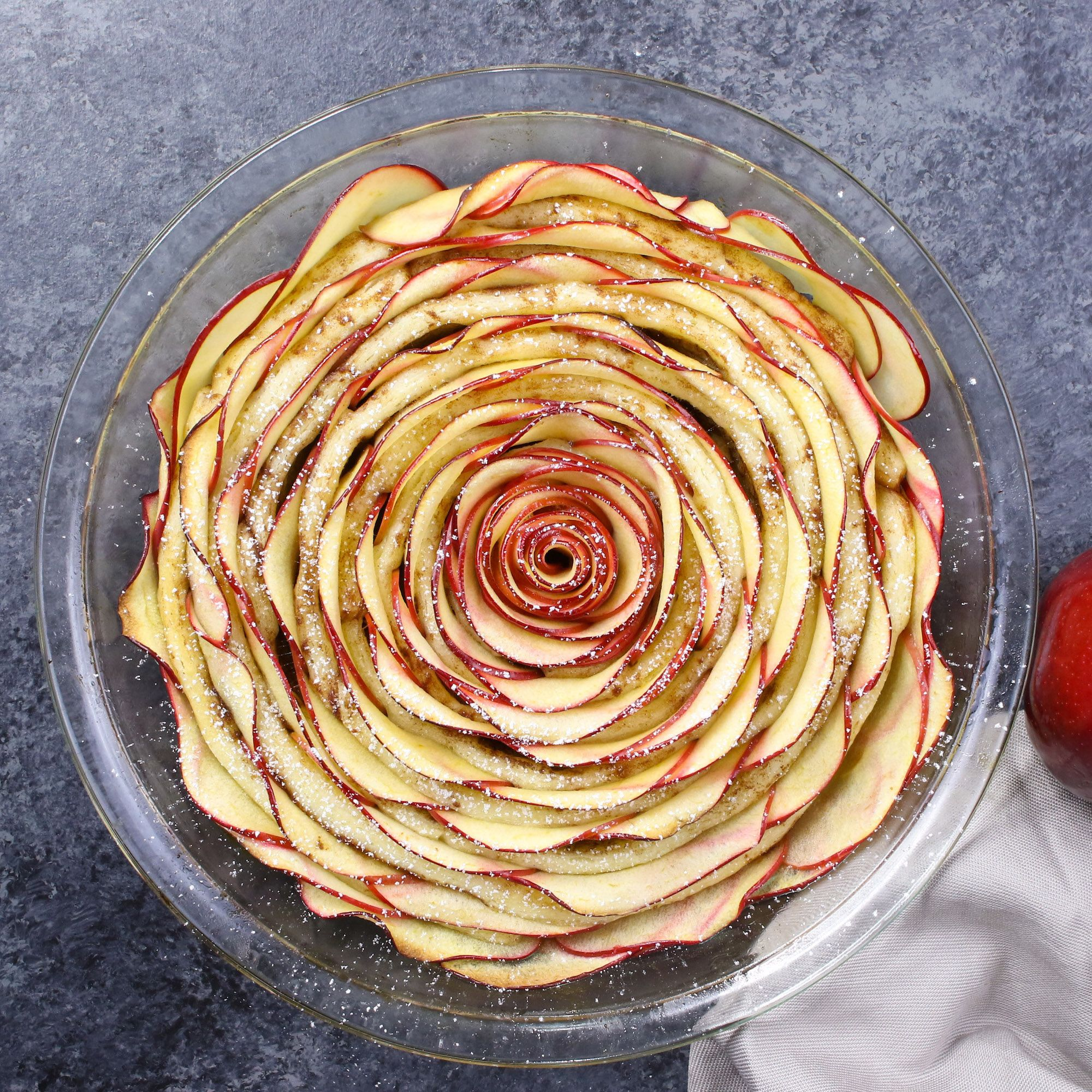 Cinnamon Roll Apple Rose Tart - Made with fresh apples. All you need is only 5 simple ingredients: cinnamon roll dough, red apples, lemon juice, brown sugar and butter. So beautiful! Quick and easy recipe. #applerecipes