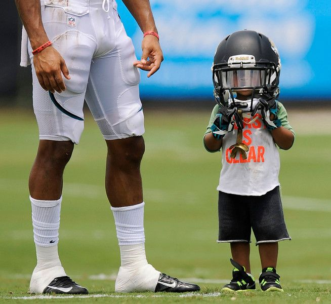 Cecil Shorts IV, 2, sports his father Jacksonville Jaguars' Cecil Shorts III's helmet during NFL football training camp Wednesday, July 31, 2013, in Jacksonville, Fla. (AP Photo/The Florida Times-Union, Bob Self)