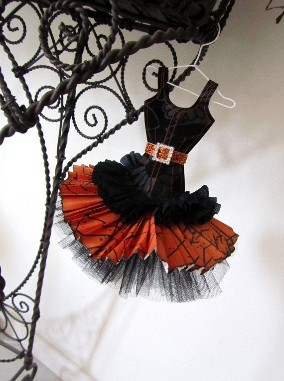 This pretty dress miniature is made from crepe, and scrapbook papers.  The bodice detail is carefully stitched in orange cotton on a flock-lined black scrapbook paper, giving it the appearance of black velvet.  The orange and black cobwebbed skirt features a black crepe ruffle, and a ruffled undershirt skirt in black tulle. It has a glitzy burnt orange belt with a sparkly diamante buckle in a square shape.