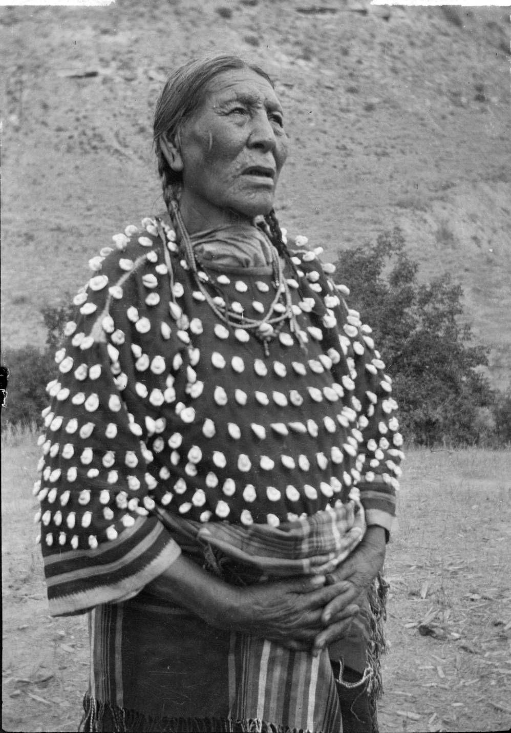 Elder Cheyenne woman standing in a field wearing a cowrie shell dress.