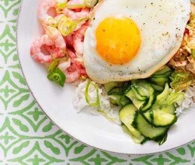 """Den koreanska risrätten """"Bi Bim Bap"""" serveras i en skål med ris toppat med olika tillbehör. På toppen ligger ett stekt ägg. Rätten serveras vackert upplagd men rörs sedan ihop i portionsskålen så att den krämiga äggulan blandas in i hela rätten."""
