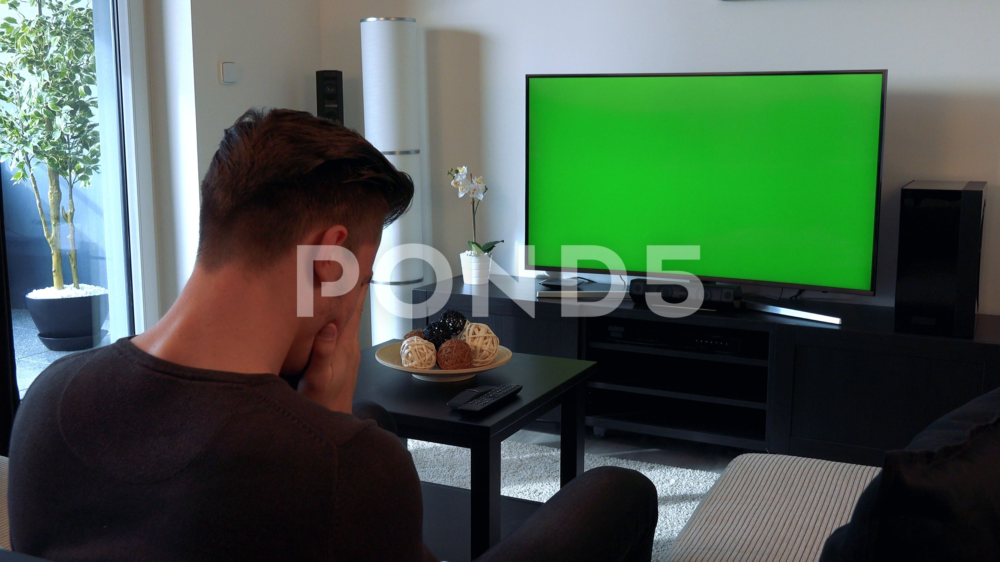 A Man Watches A Tv With A Green Screen In A Cozy Living Room And Then Buries His Stock Footage Ad Green Screen Man Greenscreen Cozy Living Cozy Living Rooms
