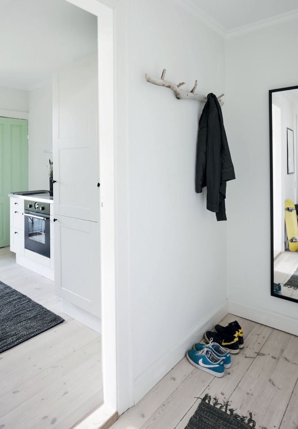 Simple entryway with minimum of decor, but with a cool and decorative coat rack of birch tree.