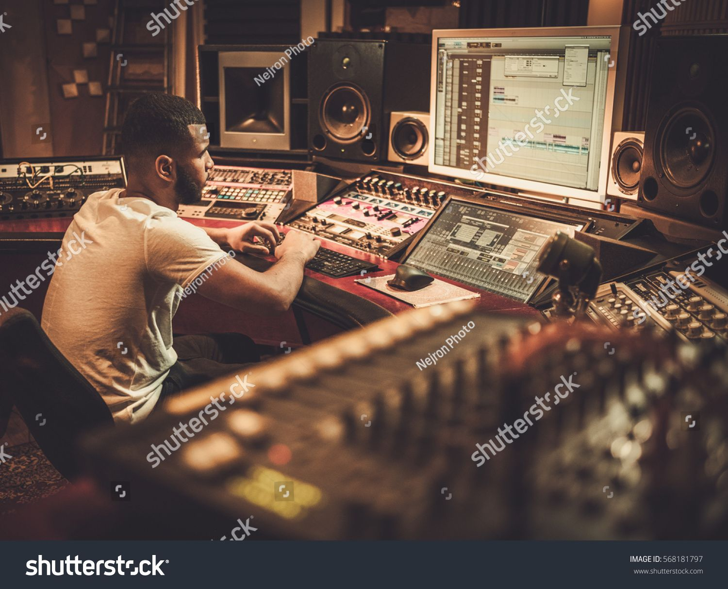 African American Sound Engineer Working At Mixing Panel In