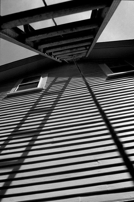'The Ladder' Standing under a ladder, the rungs mirror the building's siding in this original B&W photograph. The result is a moving and yet eerily still scene that is captivating.