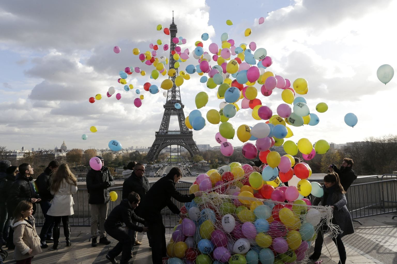 Balloons are released into the air in front of the Eiffel