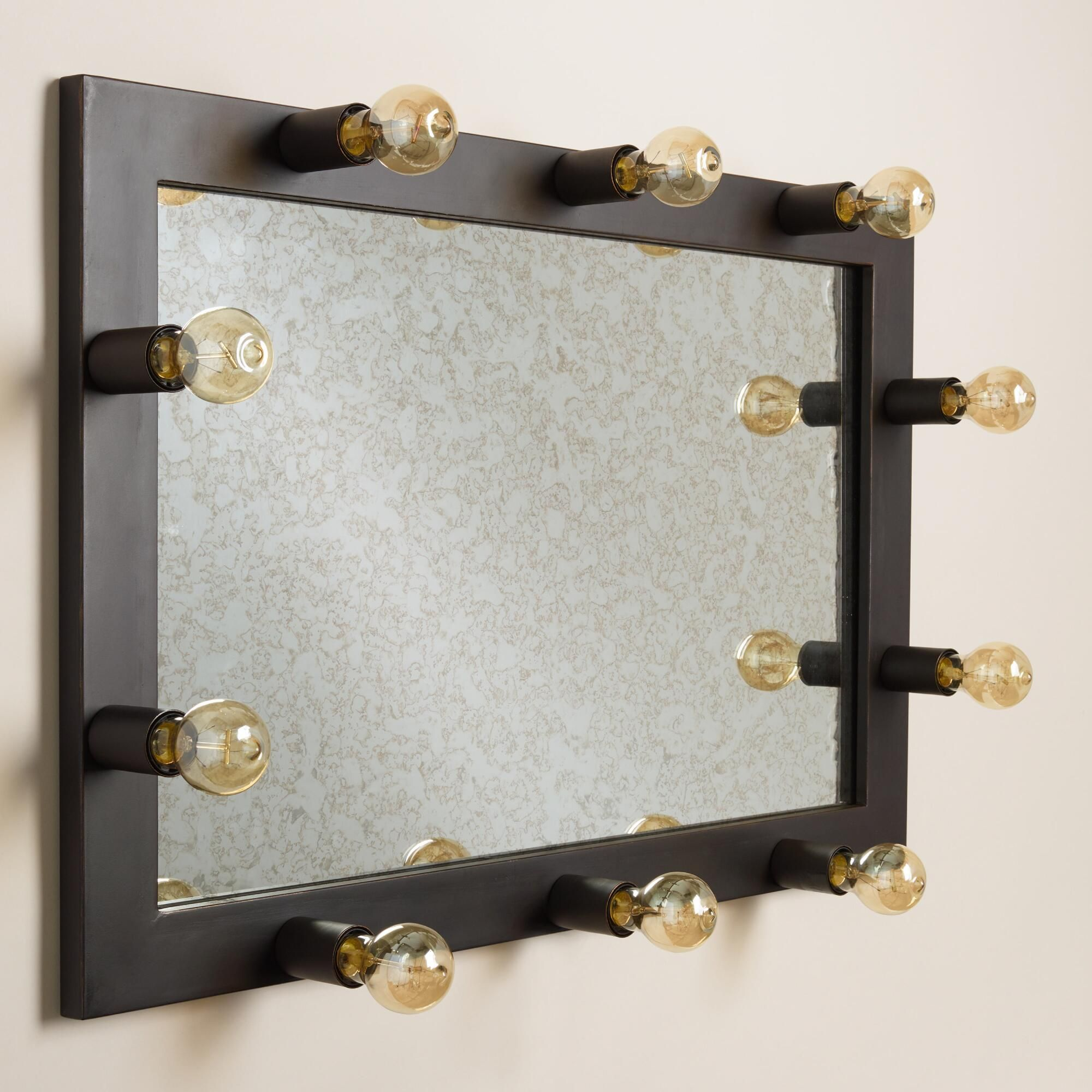Featuring an antiqued mirror surface framed with 10 Edison-style filament bulbs, our exclusive vanity mirror captures and recreates vintage Hollywood glamour. A fantastic value with all bulbs included, this fun retro accent hangs horizontally on a wall or props vertically on a flat surface.