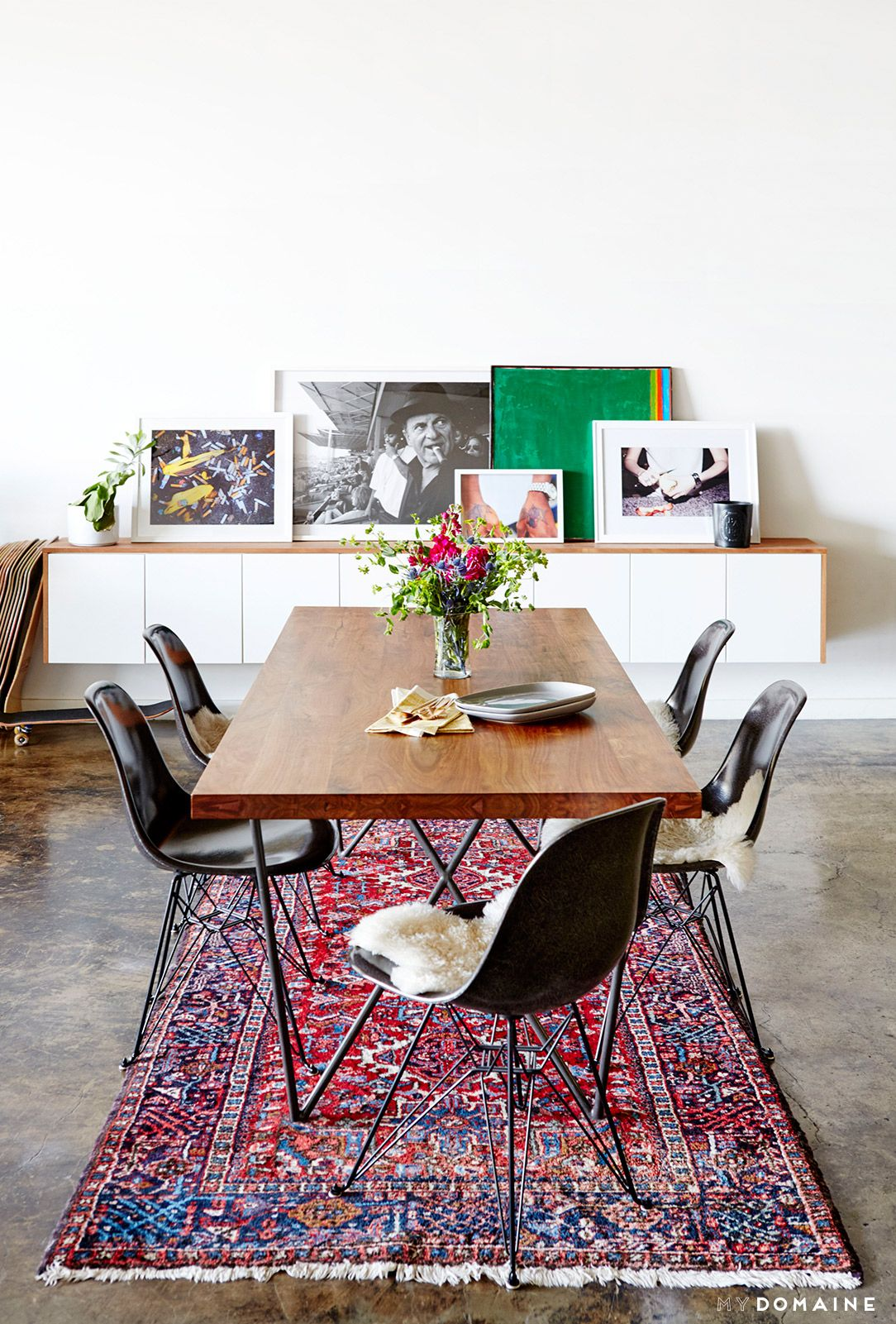 An Industrial And Modern Dining Space With Leaning Artwork, Persian Rug,  And Wood Dining