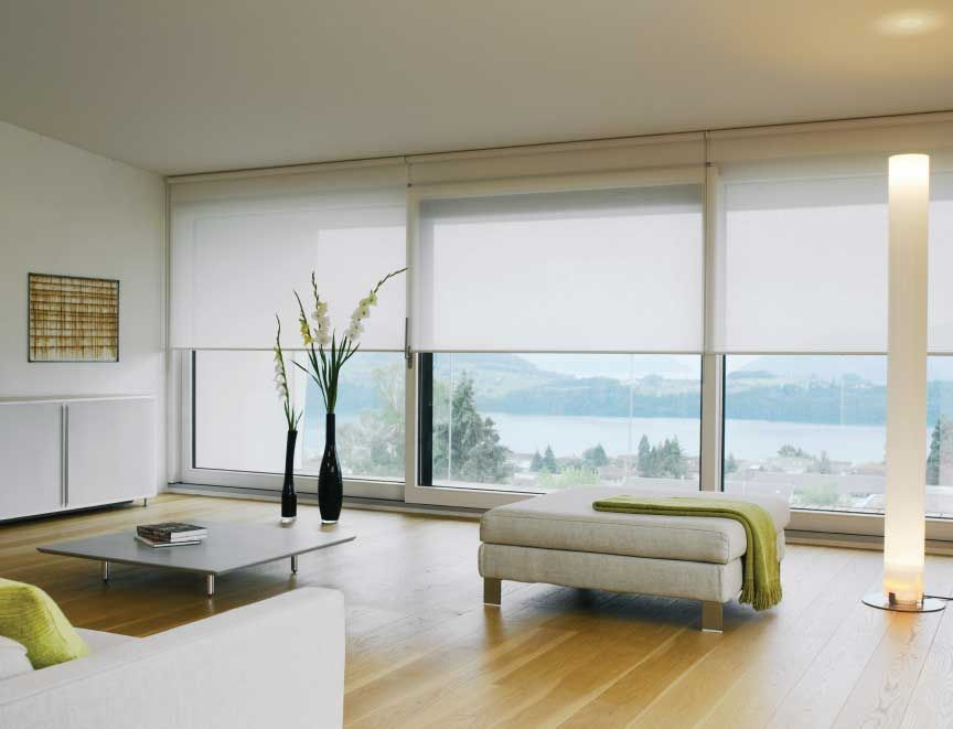White silent gliss roller blinds in an ultra modern living for Roman shades for wide windows