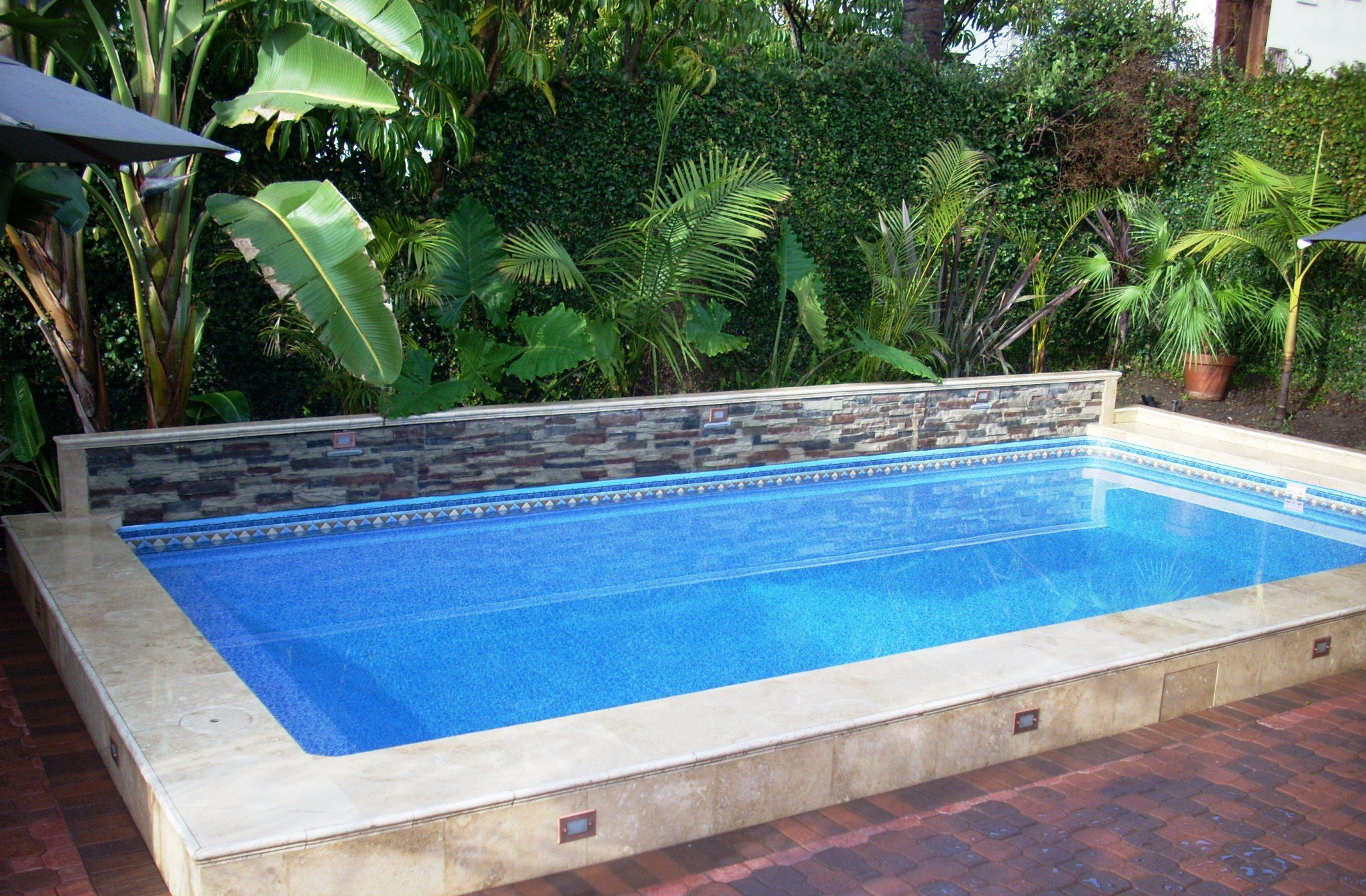 This Islander Pool Is 14 X 28 With A Raised Back Ledger Stone Wall And Lower Travertine Tile Finish The Vinyl Lined Basic
