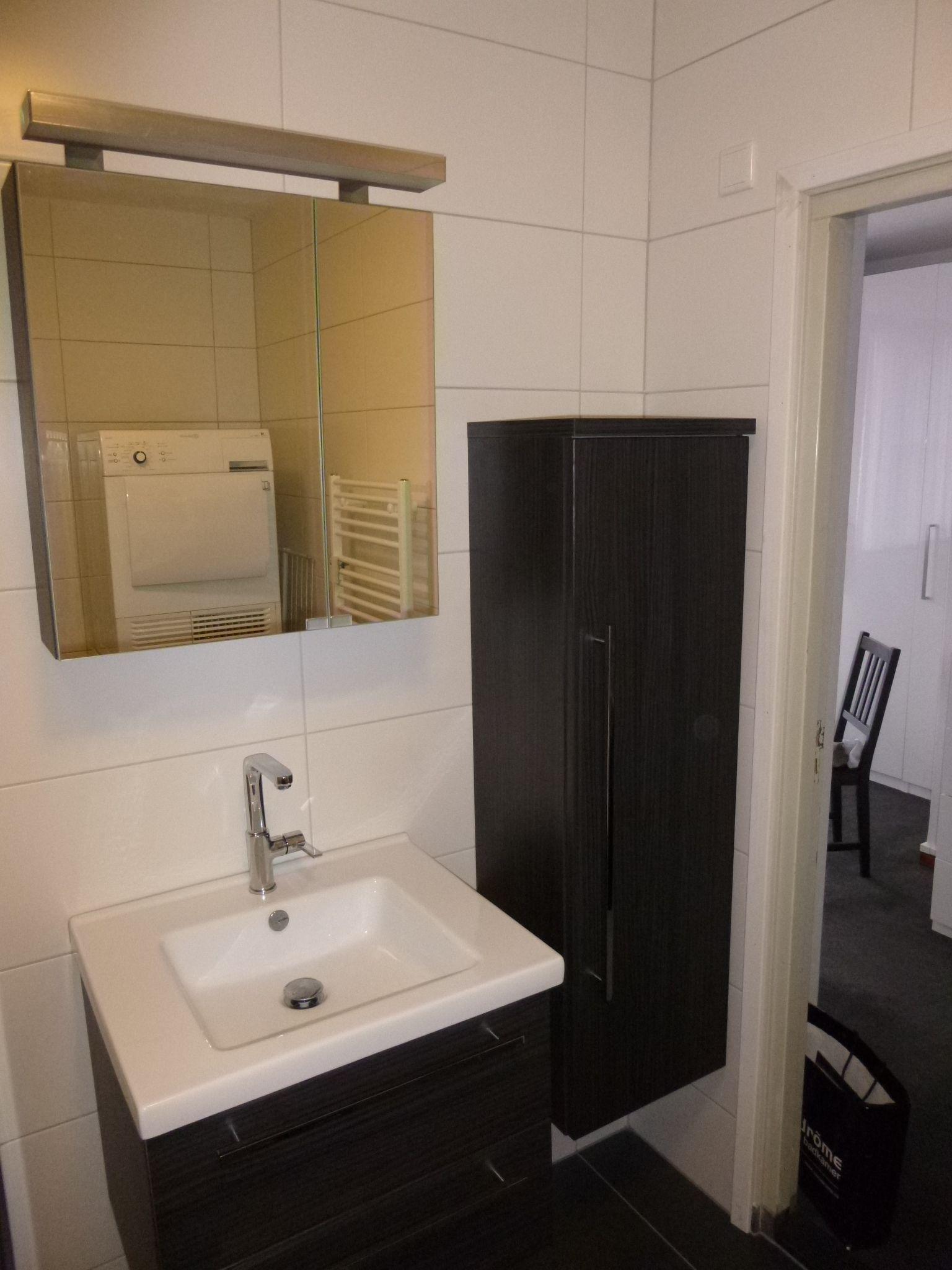 gerealiseerde badkamer met badmeubel hoge kast en spiegel door