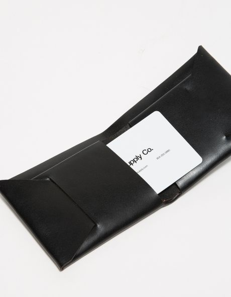 A handcrafted, stitch-less wallet from M&U Co. in black. Features single piece of leather design, cash sleeve, two card pockets, American-made bridle leather, heat-pressed logo and rectangular silhouette.   •	Stitch-less wallet in black •	Handcrafted
