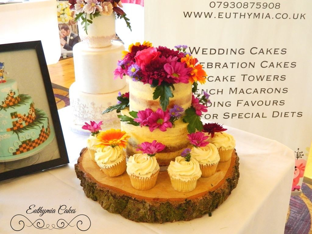 Semi naked vanilla wedding cake and cupcakes with fresh flowers by ...