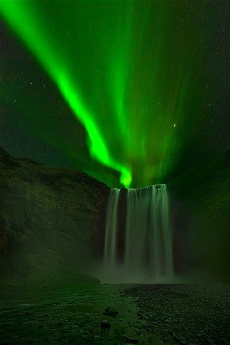 Image: Aurora borealis above a waterfall in Iceland. (© David Martin Castan/Solent N/Rex Features)