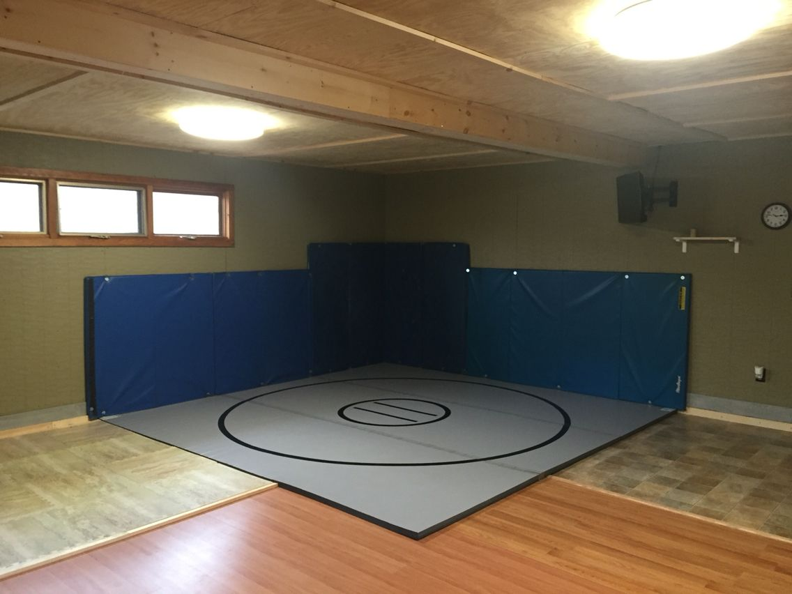 Home gym with wrestling mat lodge in man