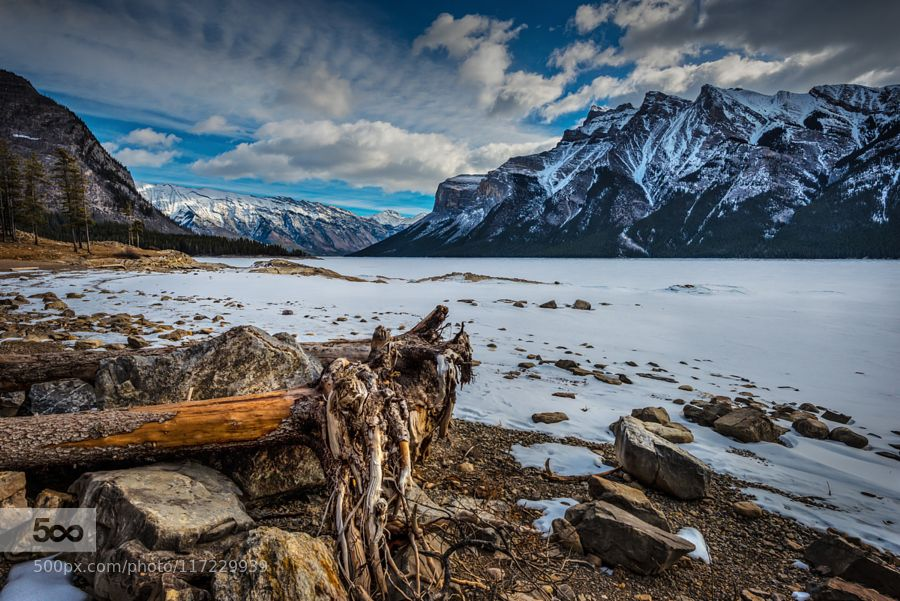 Lake Minnewanka - Pinned by Mak Khalaf From my spring trip to Banff Lake Minnewanka which means 'Water of the spirits'... or in this case the frozen water of the spirits... ;) Landscapes albertabanffcanadacloudslakelandscapesmountainmountainsskysnowsunsetwaterwinter by Bob_Bittner
