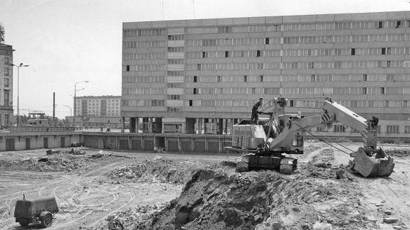 magdeburg | Ein Bagger steht am Rand einer Grube, im Hintergrund ein Hochhaus