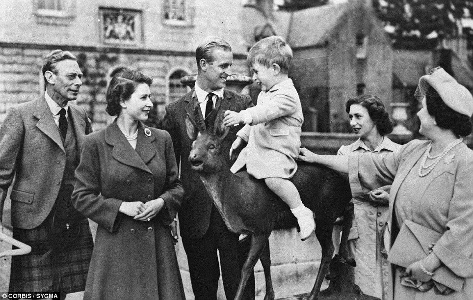 Amusing: Prince Charles gets a ride on a deer sculpture watched closely by the Queen, King George VI and the Queen Mother, while Prince Phillip