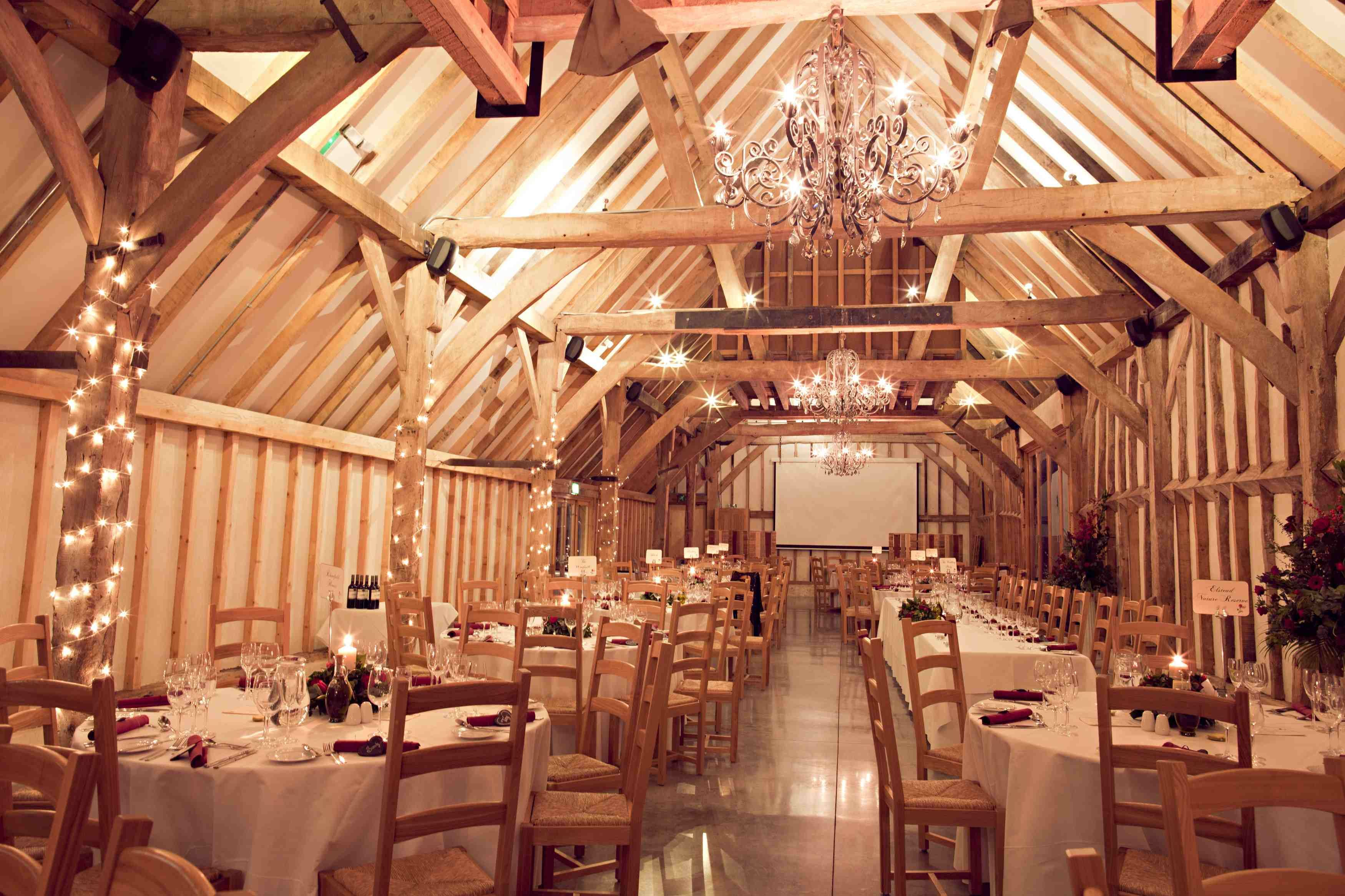 Fairy lights wrapped around the barn beams create a ...