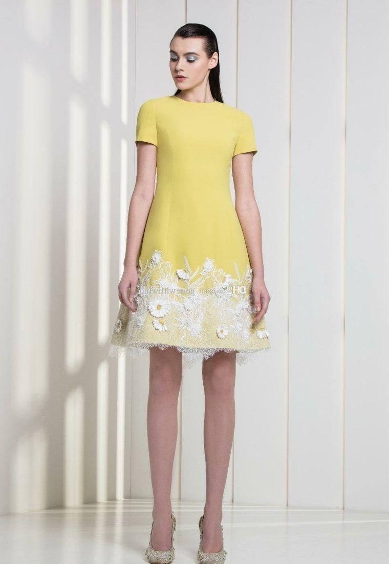 5e95ea6ee492 Donna vestita con un abito di colore giallo corto e decorato con pizzo  bianco nella parte
