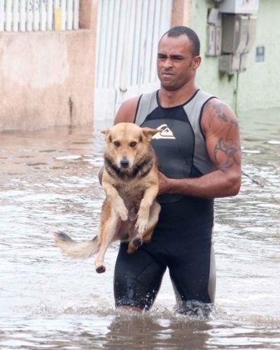 24.dez.2013 - Morador salva cachorro em rua alagada no bairro Jacaraípe, em Serra, Espírito Santo. Chuvas fortes causaram mortes e deixaram milhares de desabrigados no Estado.