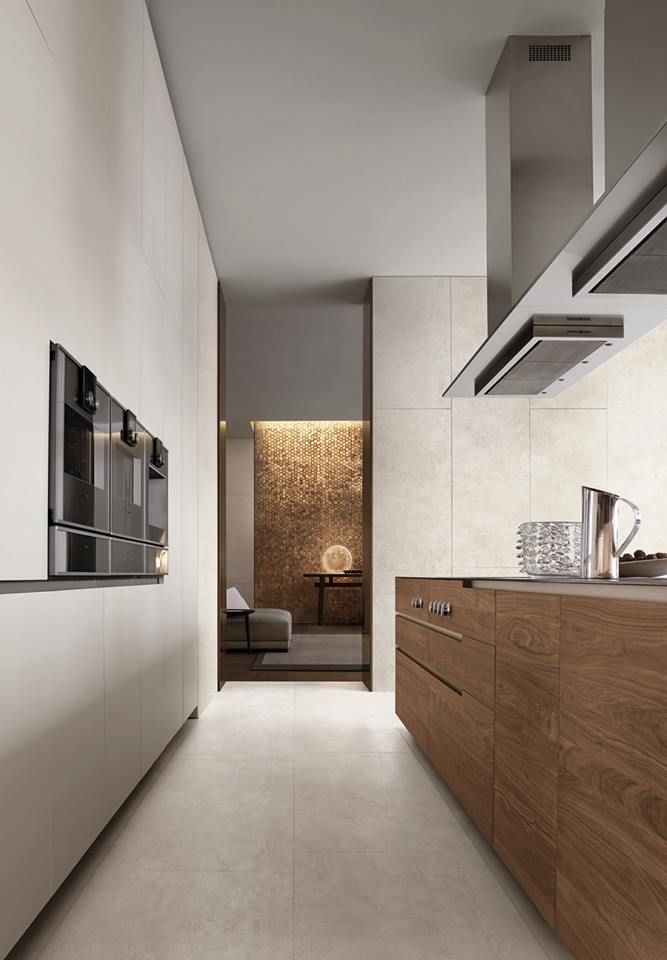 Phoenix kitchen, base units with doors, drawers and pull-out storage baskets in walnut canaletto solid wood, top in Scholtès steel. Island hoods in steel.