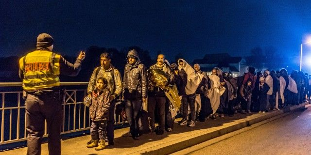 "LKS 20151026  REG010; TOPSHOTS Policeman (L) gestures as refugees wait in line on the Innbruecke bridge at the German / Austrian border at Simbach am Inn, southern Germany on October 25, 2015. Germany faced a new influx of migrants in Bavaria on the border to Austria, where police said to be ""overwhelmed"" with the number of refugees who flocked during the weekend. LEHTIKUVA / AFP PHOTO / DPA / ARMIN WEIGEL +++"