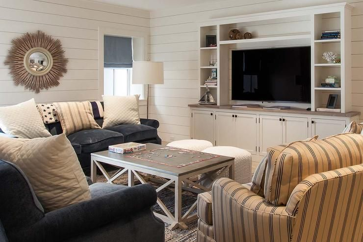 chic family room features walls clad in shiplap lined with a built