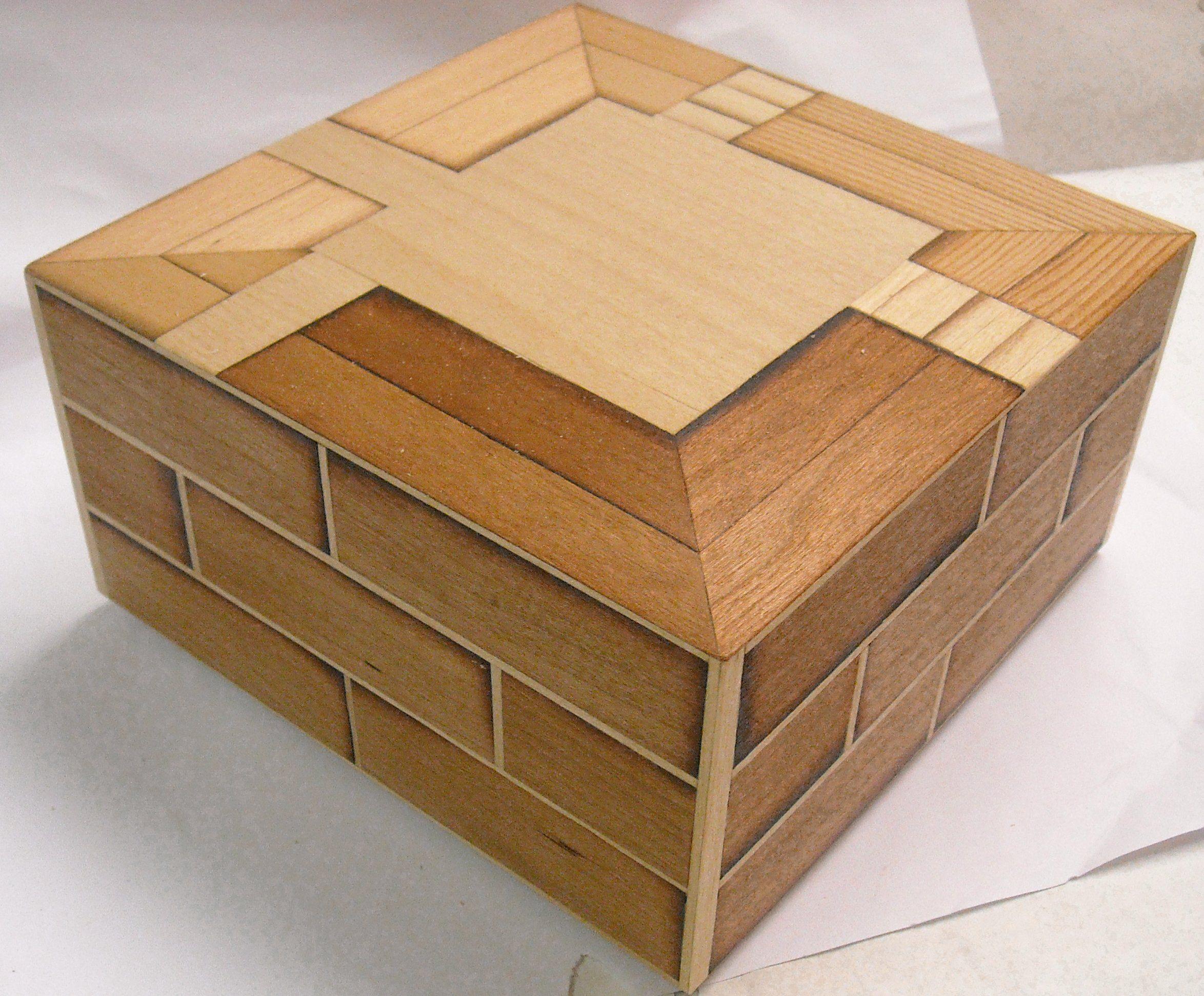 Tässä tiiliseinää sivuissa ja kortteli- ilmakuvaa kannessa. Intarsiatekniikalla puusta tehtynä.